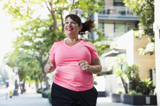 Cheerful woman jogging on footpath in city