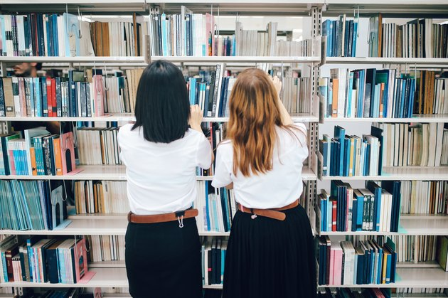 Two women searching for books in the library
