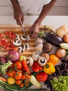 Woman on a weight-loss diet chopping a variety of vegetables in her kitchen