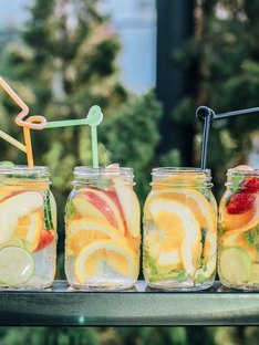 six fruity waters with sliced fruit and straws on table