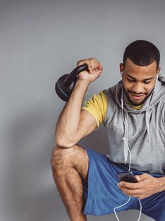 Man listening to workout music holding a kettlebell