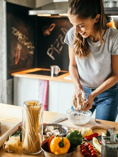 Young woman in the kitchen cooking with healthy alternatives