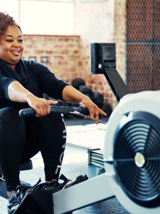 Woman doing a cardio workout on the rowing machine at her gym