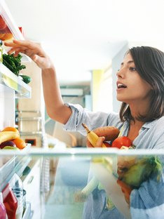 Woman picks out a handful of fruits and veggies from the fridge
