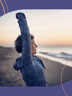 A woman with arthritis stretching on the beach