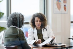 woman doctor in white coat reviews a patient's medical records in glass conference room