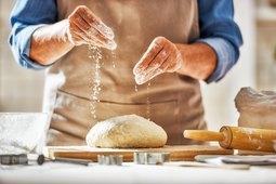 Hands preparing dough in kitchen for bread