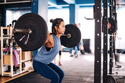 woman doing barbell squat for best lower-body workout