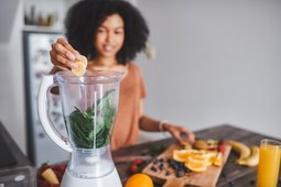 Woman placing fruit into blender with spinach for smoothie