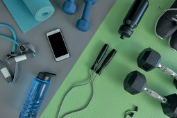 Top view of exercise equipment, including dumbbells, jump rope, resistance bands and green yoga mat