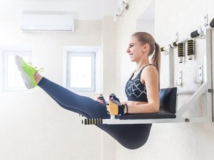 Woman doing hanging leg lifts on the captain's chair at the gym during her ab workout