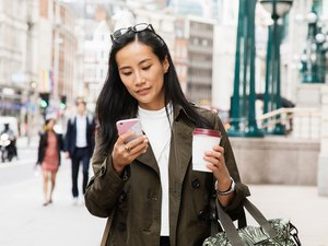 Woman walking down a busy city street looking at her phone.