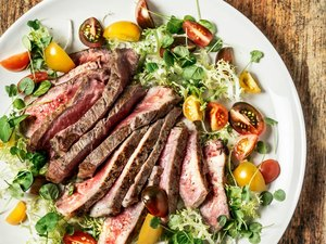 A Whole30 Diet dinner of steak over salad