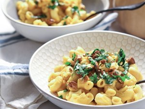 Two bowls of golden macaroni noodles topped with parsley and almonds.