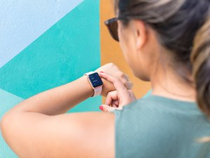 woman checking Apple watch to count 7,500 to 10,000 steps a day during a walking challenge