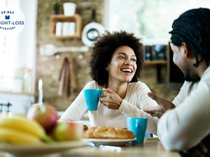 happy couple eating a healthy filling breakfast to avoid overeating later