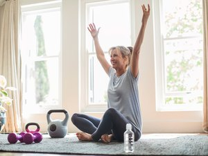 woman doing weight-loss workout at home on yoga mat