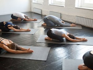 People in yoga class doing child's pose spinal stretch