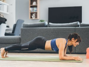 Woman performing plank workout at home with no equipment