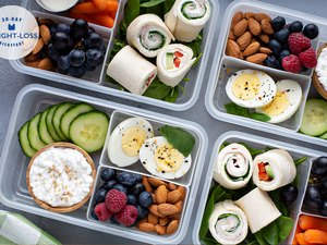 meal prepped lunches in containers with hard boiled eggs cucumbers and fresh fruit and nuts