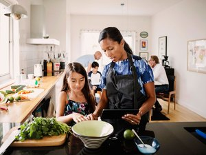 Woman and daughter in kitchen cooking from recipe with cooking tips and cooking hacks