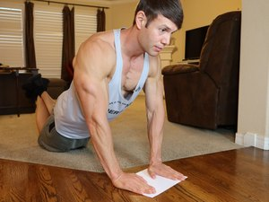 Man using a sheet of paper to do a workout