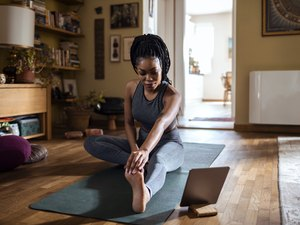 Woman is stretching before starting an at-home yoga flow