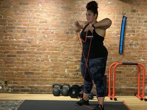 Woman doing an upright row with a resistance band during a shoulder workout