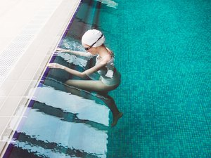 Woman starting to swim in a pool wearing goggles and swim cap