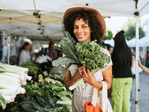 Woman holding bunch of kale at farmer's market