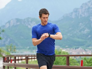 Man running outside in the mountains looking at running watch.