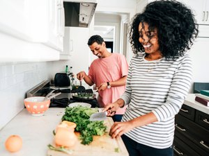 Couple using cooking tips and cooking hacks for healthy cooking in kitchen