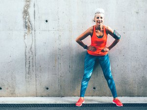 Woman standing against a concrete wall wearing colorful activewear