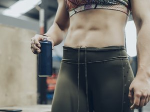 close up of woman's midsection at gym holding a blue canned drink