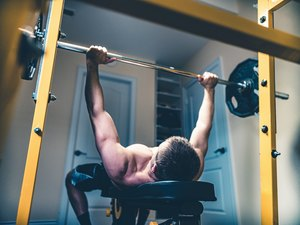 photo of man lifting weights doing bench press