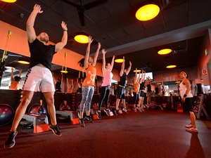 group of people participating in an Orangetheory Fitness workout class