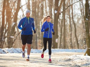 Couple in winter workout gear running together outdoors