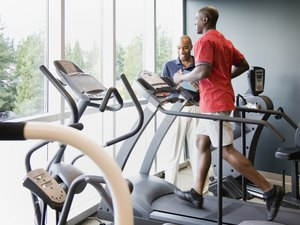 Personal trainer coaching man on treadmill during a winter run