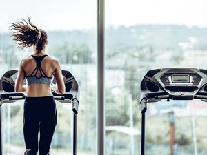 Attractive woman running on treadmill in sport gym.