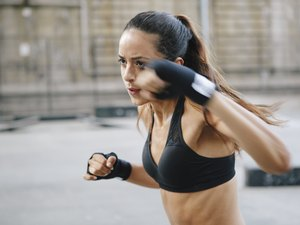 Young woman in sports bra and wrist wraps doing boxing HIIT workout outside
