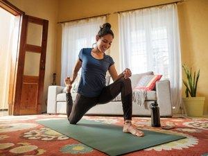 Woman stretching her hips on mat in living room for joint mobility