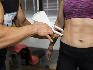 Male trainer measures body fat to a woman