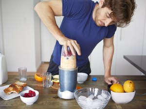 Man making smoothie in blender while standing in kitchen