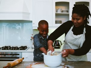 Mother and son mix dough for bread