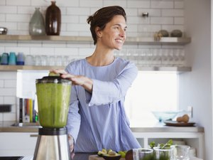 A smiling woman making a green smoothie in a blender