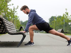 Man doing leg stretch to help prepare him for burpees