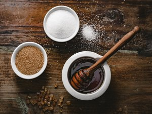 different kinds of sugar like healthy sugar substitute maple syrup on a dark background