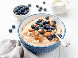 Healthy breakfast oatmeal porridge in bowl with blueberries and almonds