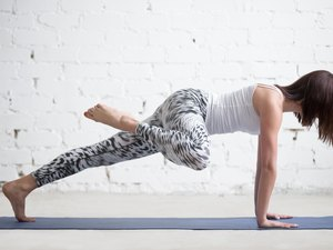 Young attractive woman in Plank pose, variation, white studio