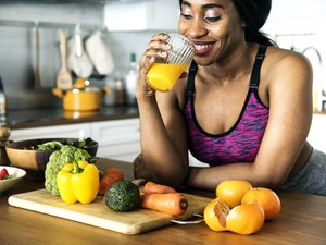 An active woman drinks a homemade electrolyte drink in her kitchen
